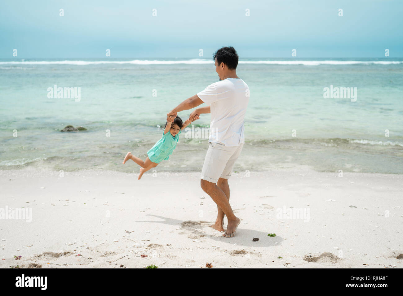 father holding daughter hands when  playing swing rotates on the beach - Stock Image