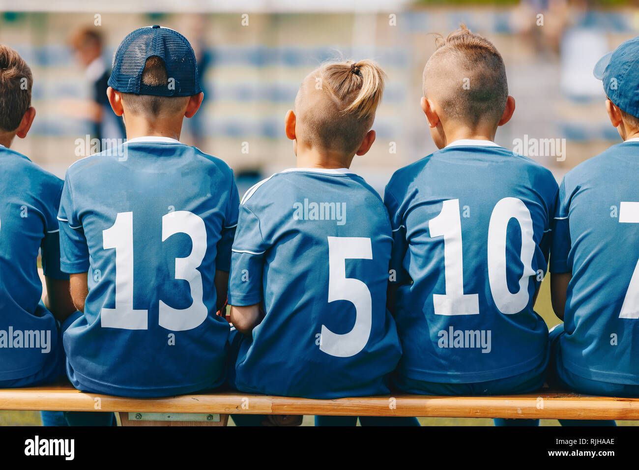Boys Sitting on Soccer Football Wooden Bench. Kids Football Team. Soccer Tournament Match for Children. Young Boys Playing European Football Game. Chi - Stock Image