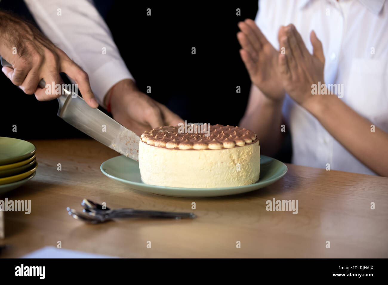 Close Up Of Man Cutting Birthday Cake In Office