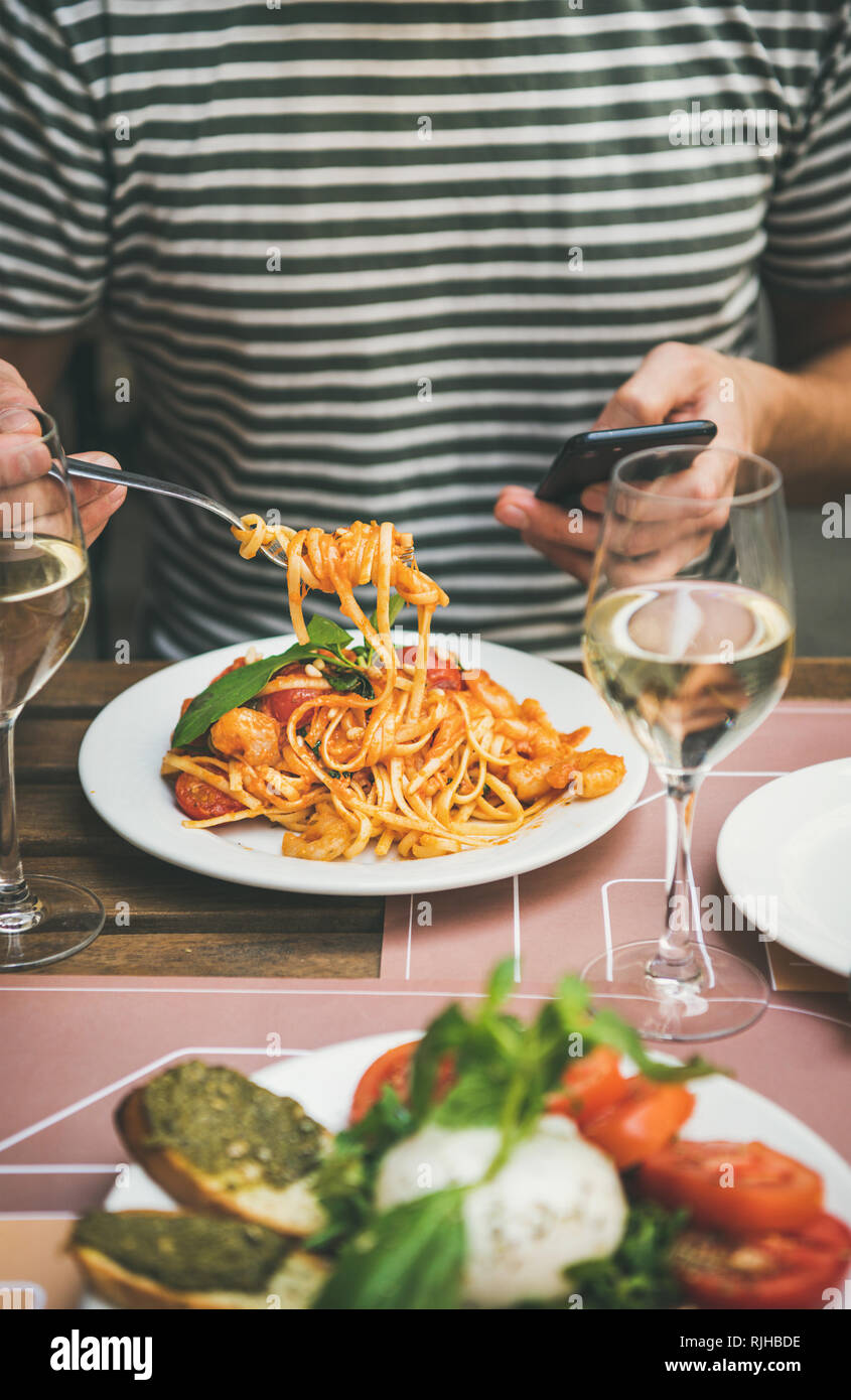 Italian dinner at bistrot with caprese and pasta with shrimps - Stock Image