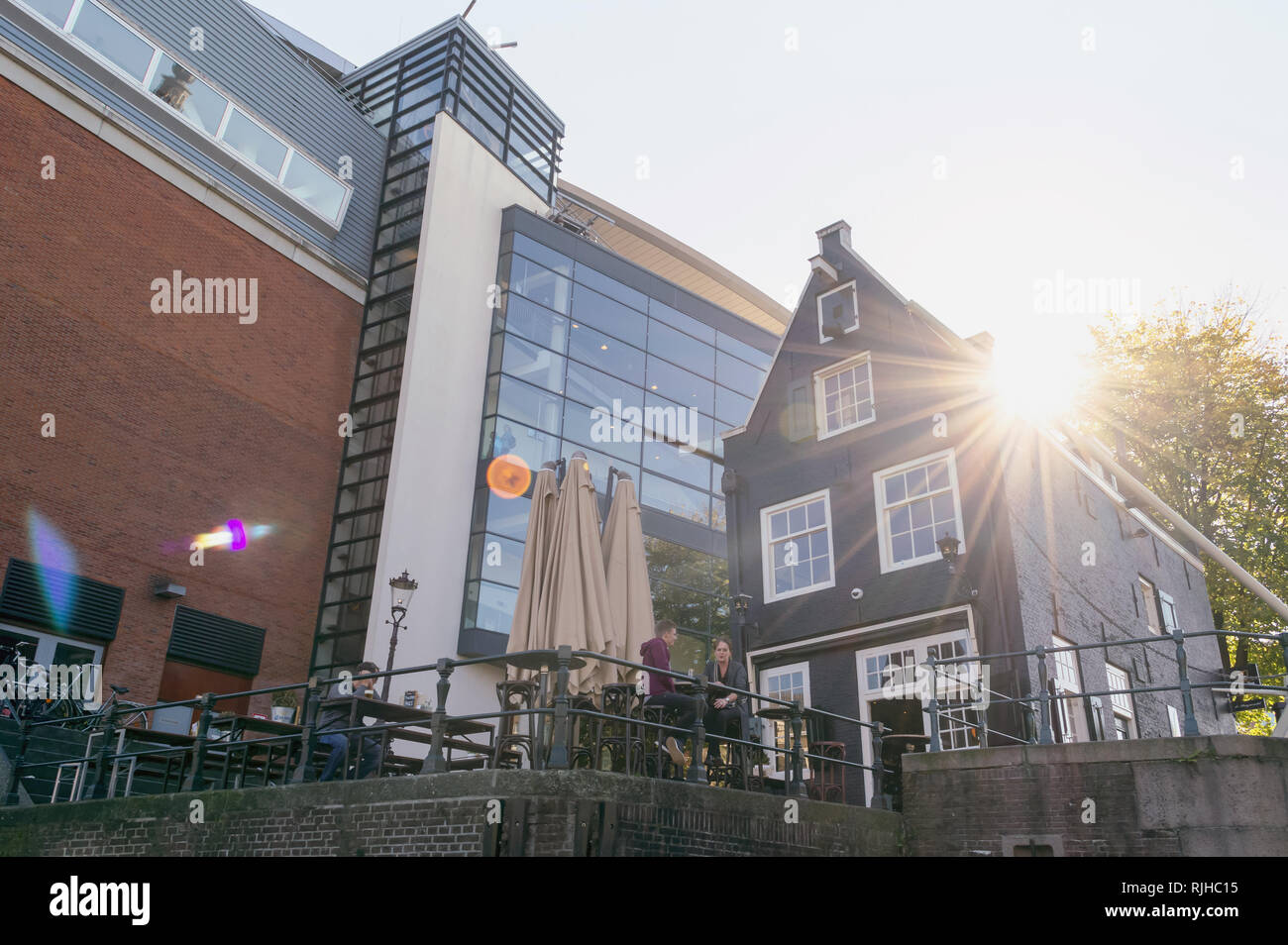 Amsterdam, The Netherlands, October 10, 2018: view from below on people at cafes table and warm sun rays shining through the roof - Stock Image