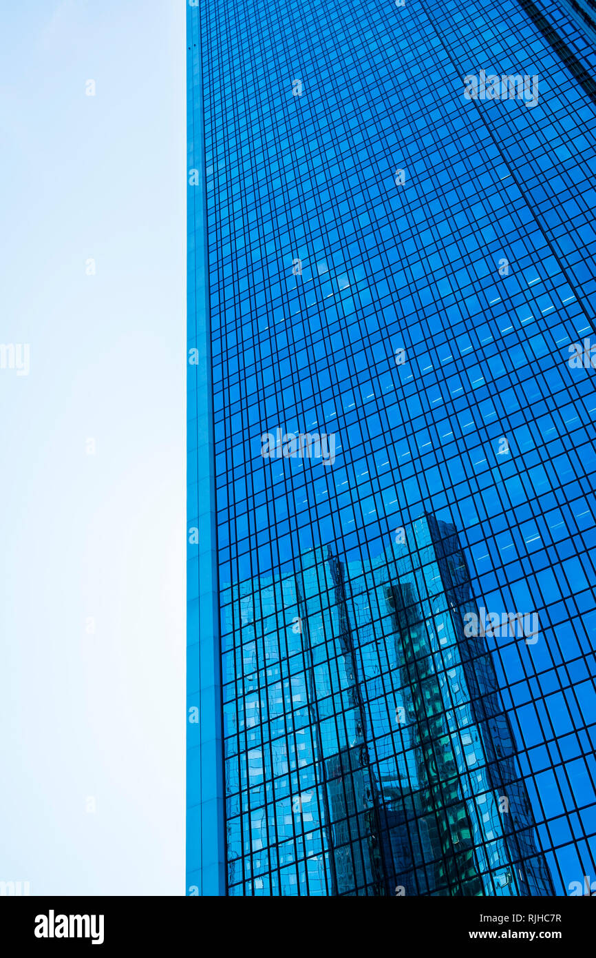 facade of high-rise office building reflecting another skyscraper - Stock Image