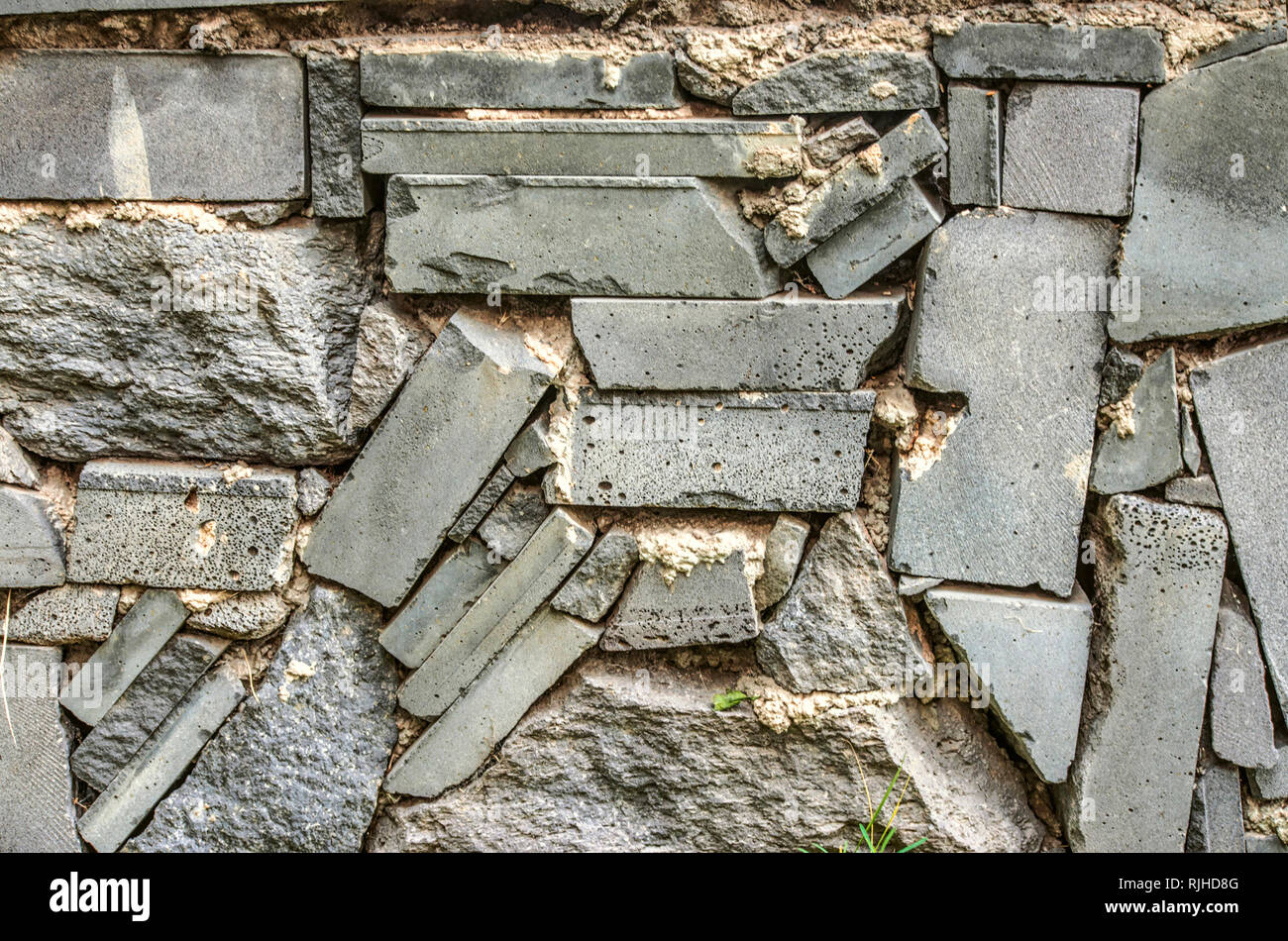 Single-color background on the fence of broken, treated basalt stone, in gray shades - Stock Image