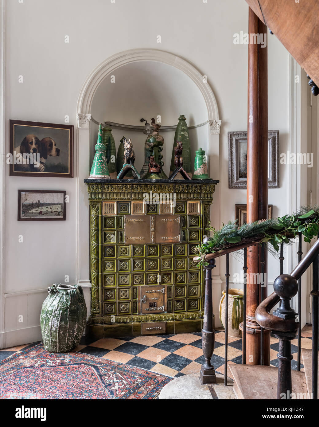 Green glazed stove in the hallway with original black and terracotta tiles - Stock Image