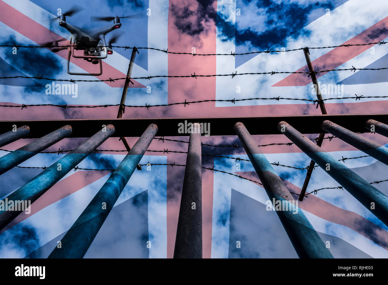 Drone flying over steel barred fence topped with barbed wire. Concept image: drugs in prisons, surveillance, spying, border control... - Stock Image