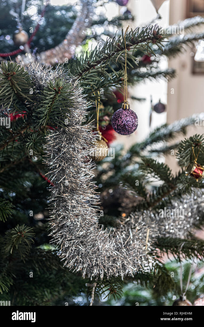 Silver tinsel and baubles on Christmas tree - Stock Image