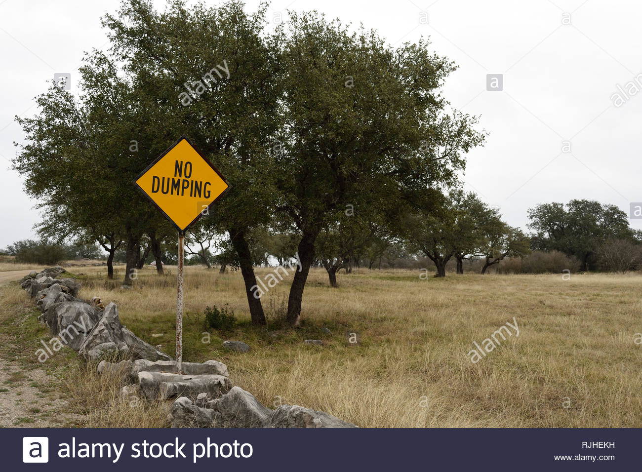 No Dumping Sign at Dead Mans Hole near Marble Falls Texas in the Texas Hill Country. No Dumping. Warning Sign. Yellow Diamond Warning Sign no Dumping - Stock Image