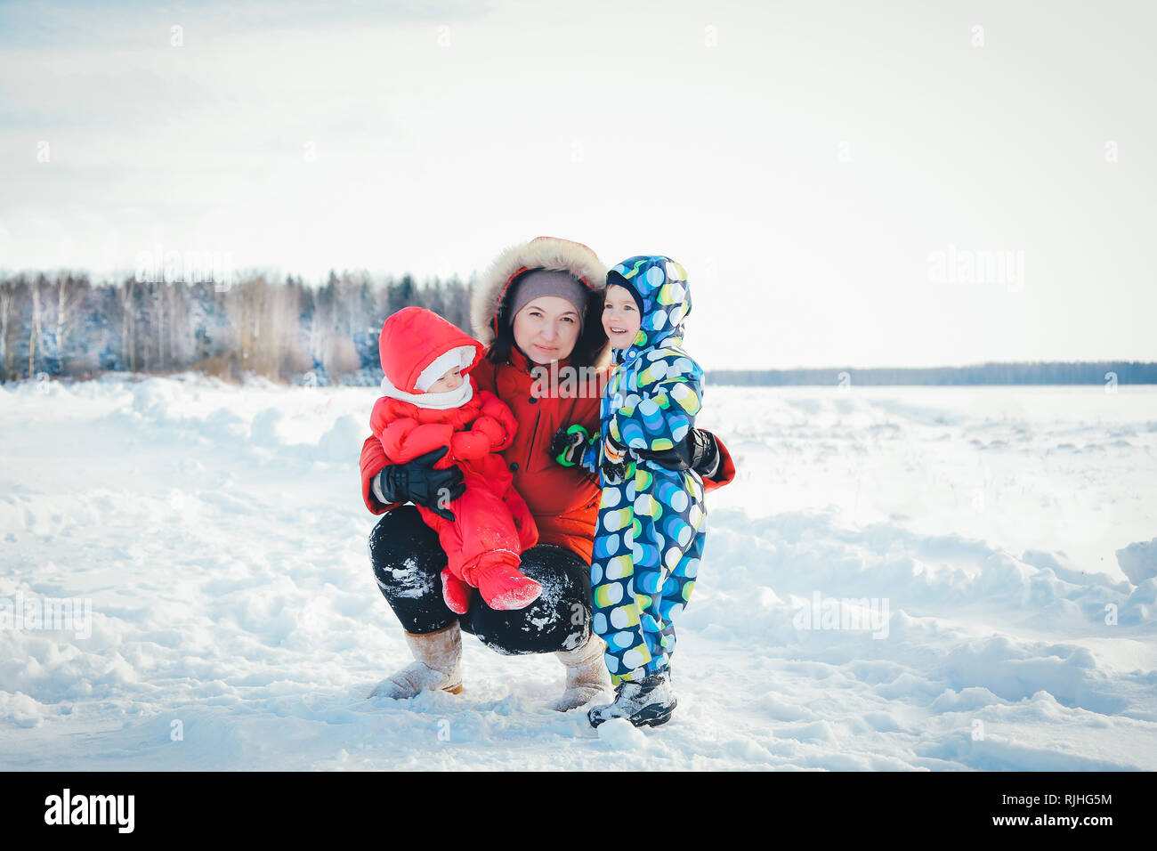 Mom daughter and son hugging on the winter walk on a cold morning - Stock Image