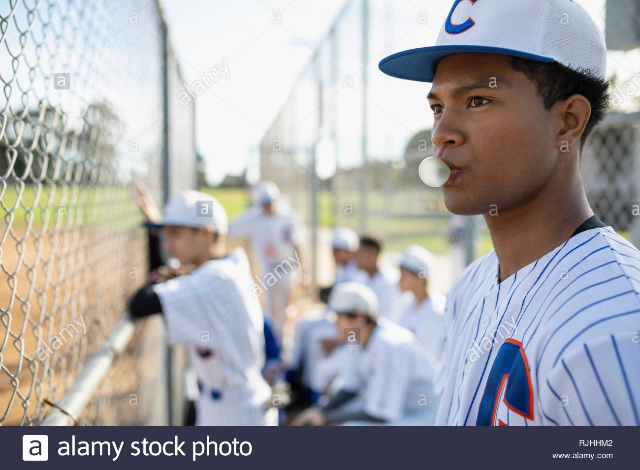 Baseball player blowing bubble gum bubble behind fence - Stock Image