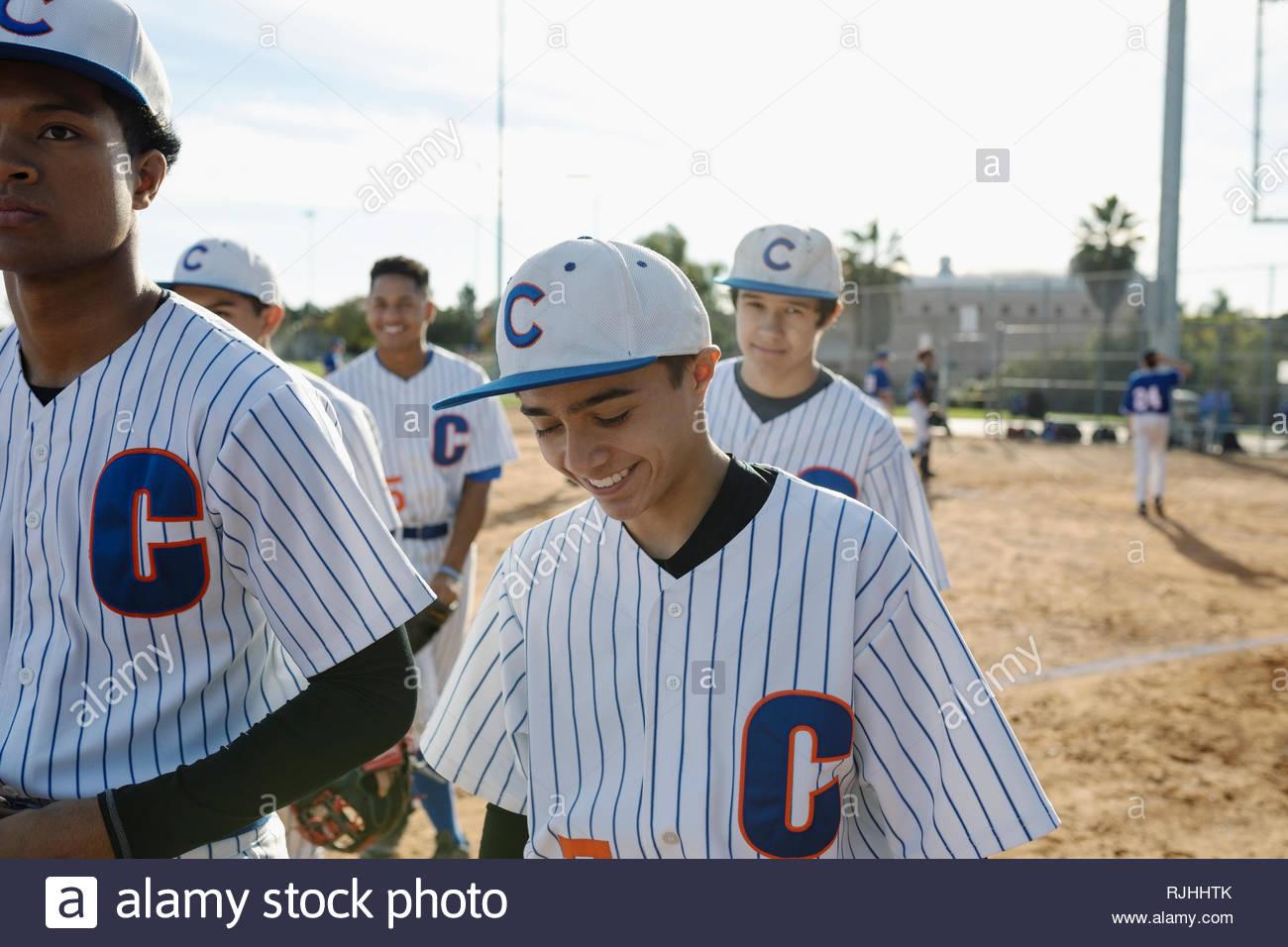 Smiling Latinx baseball player walking off field - Stock Image