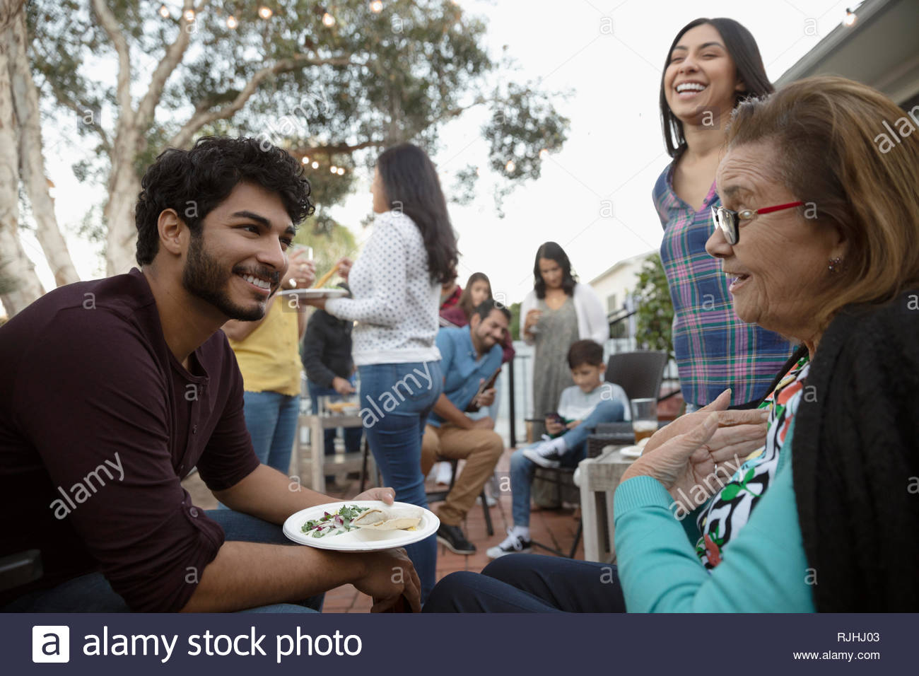 Latinx grandmother and grandson talking and eating on patio - Stock Image