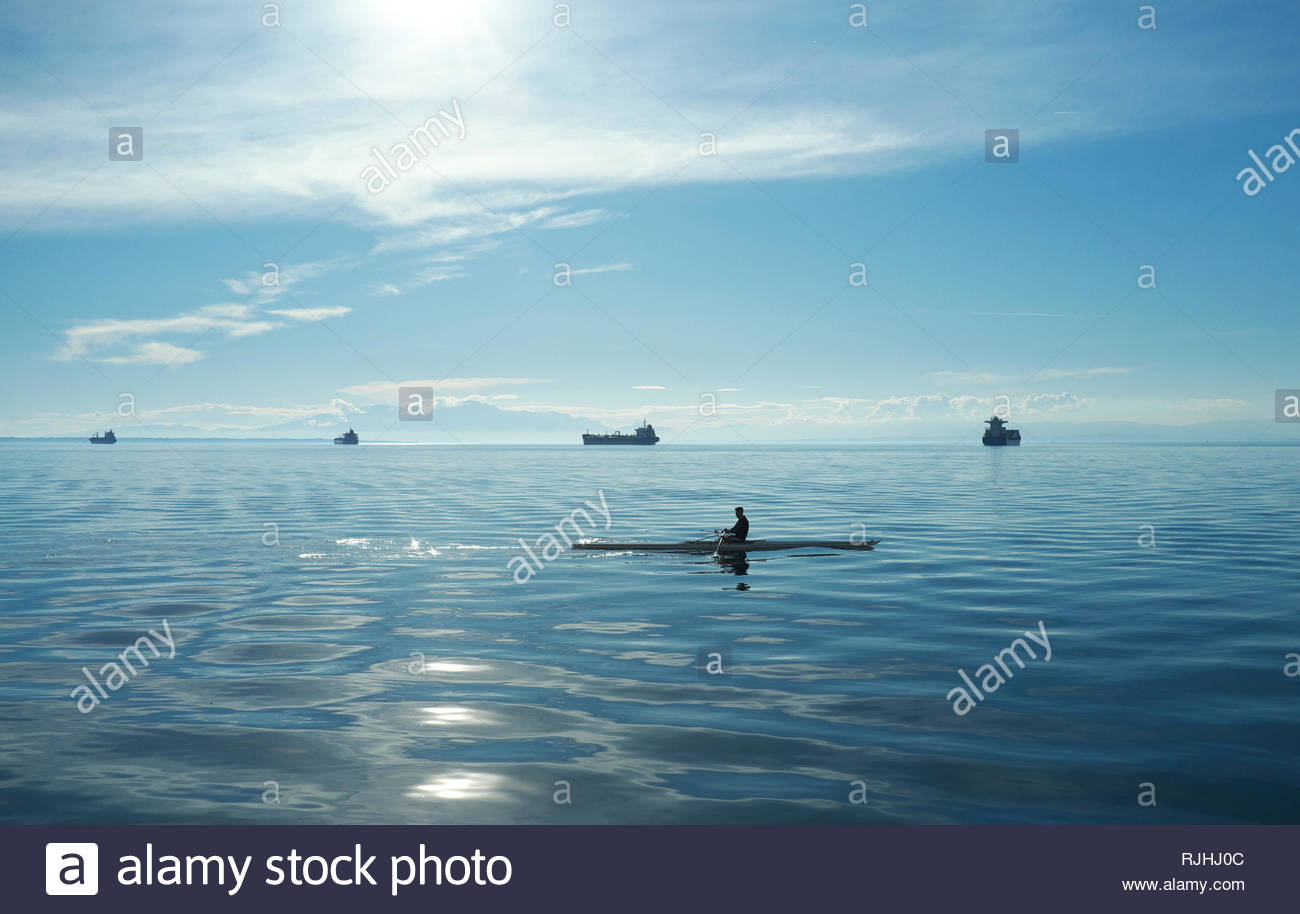 A canoeist off the waterfront in Thessaloniki, with large vessels in the distance anchored in the Aegean Sea. Thessaloniki, Central Macedonia, Greece. Stock Photo