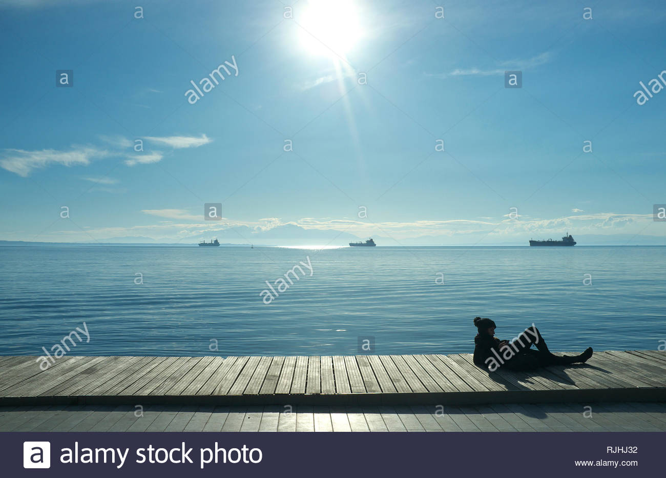 Relaxing on the waterfront in winter sunshine, in the city of Thessaloniki, Central Macedonia, Greece. Stock Photo