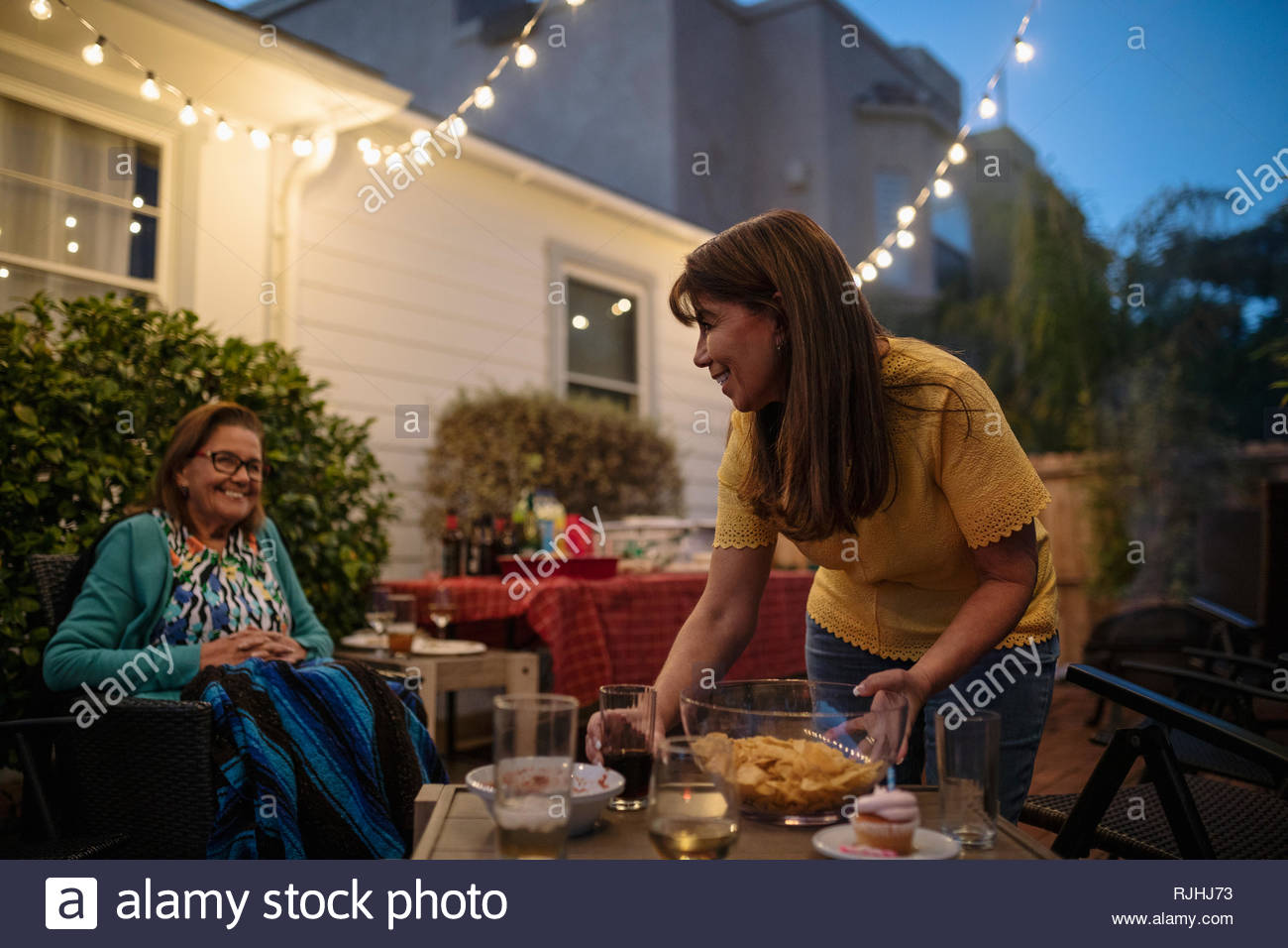 Latinx daughter and senior mother cleaning up after barbecue on patio - Stock Image