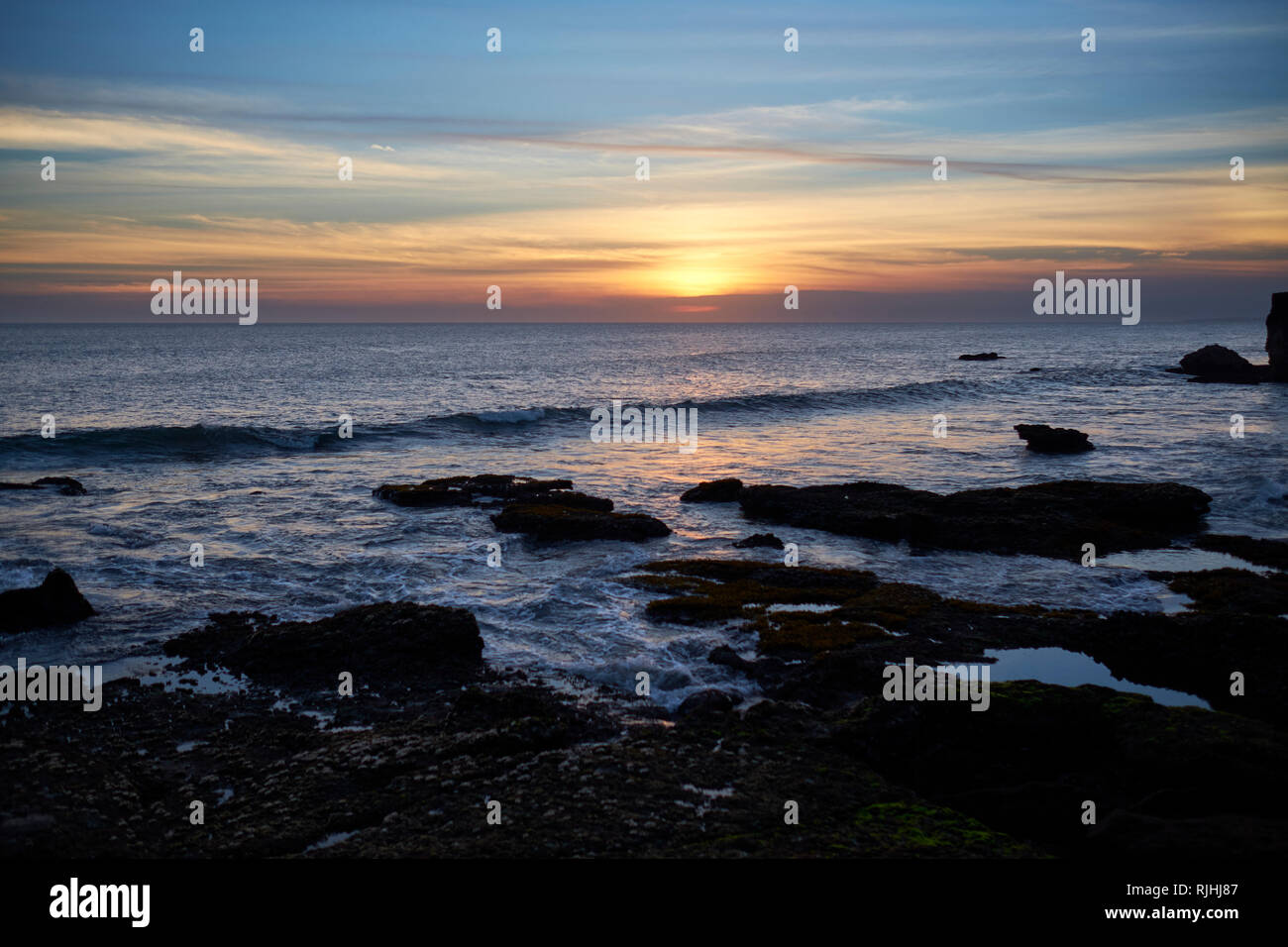 Sunset over ocean at Tanah Lot, Bali, Indonesia - Stock Image