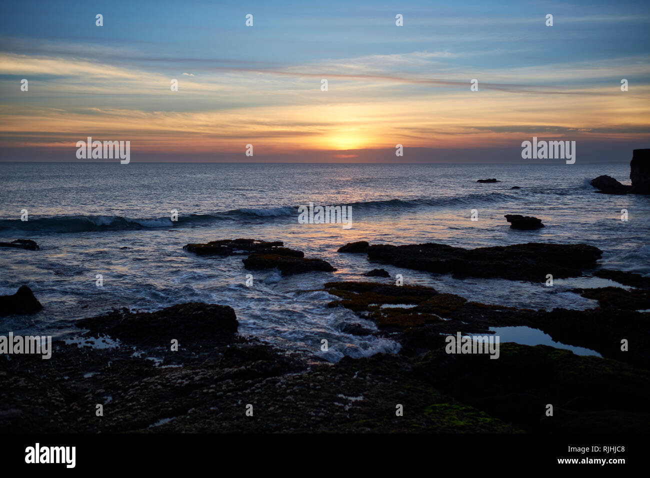 Sunset over ocean at Tanah Lot, Bali, Indonesia Stock Photo