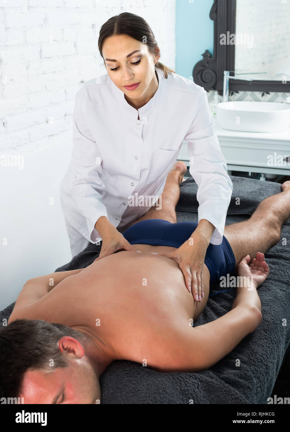 Professional masseuse performing back massage to positive american male client in spa center Stock Photo