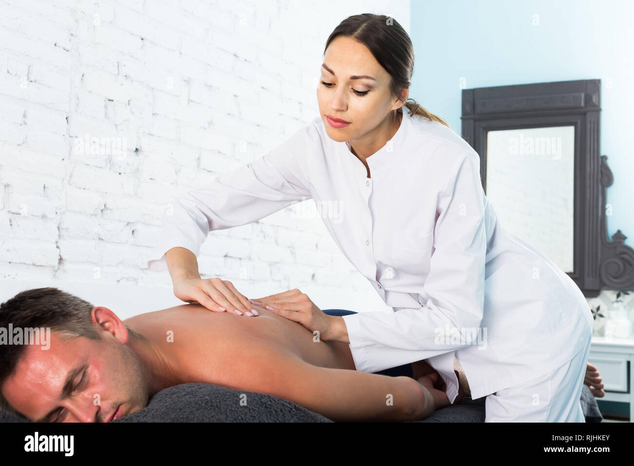 Professional masseuse performing back massage to positive male client in spa center Stock Photo