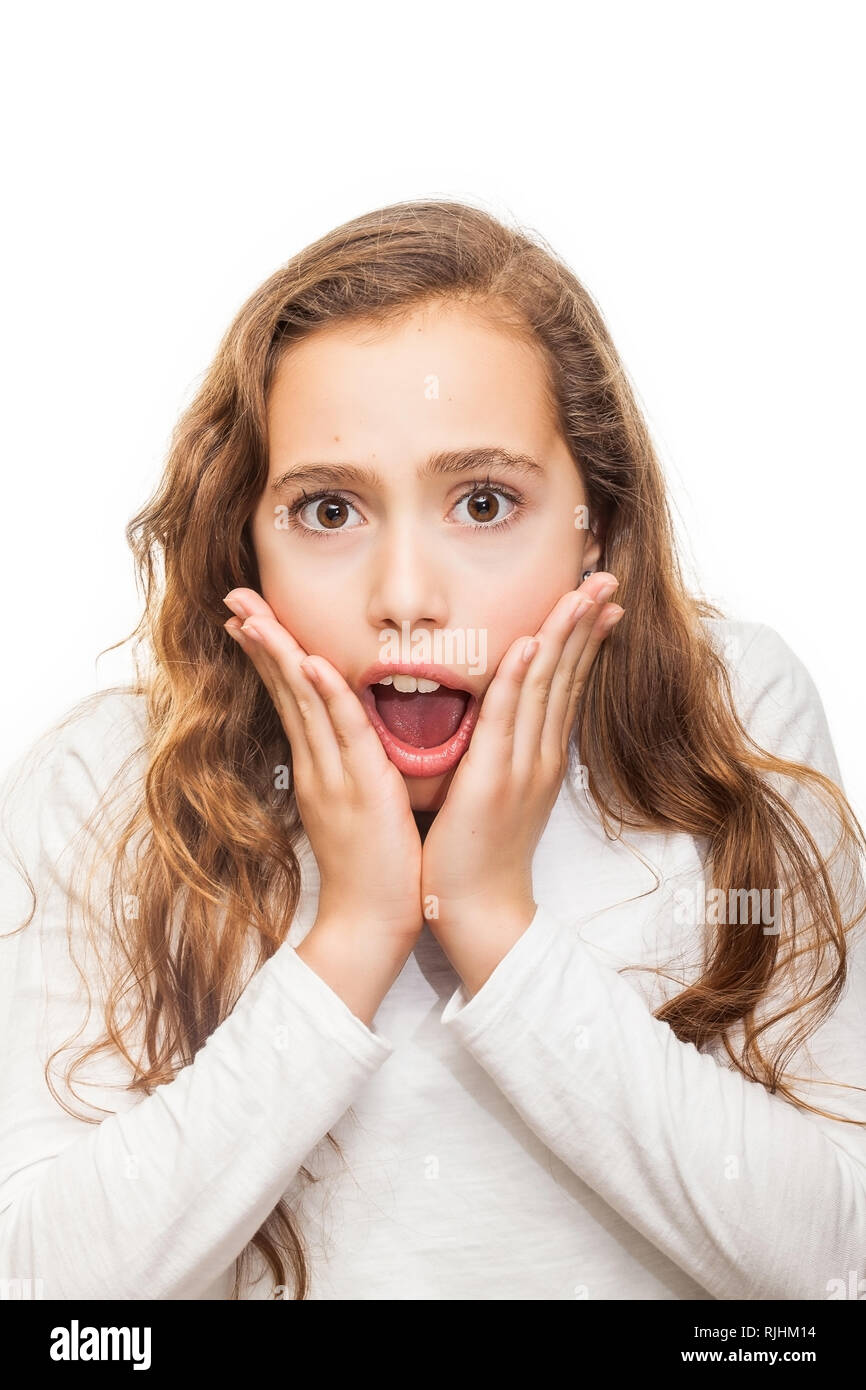 Surprised and horrified young girl looking at camera with eyes wide-opened isolated on white background - Stock Image