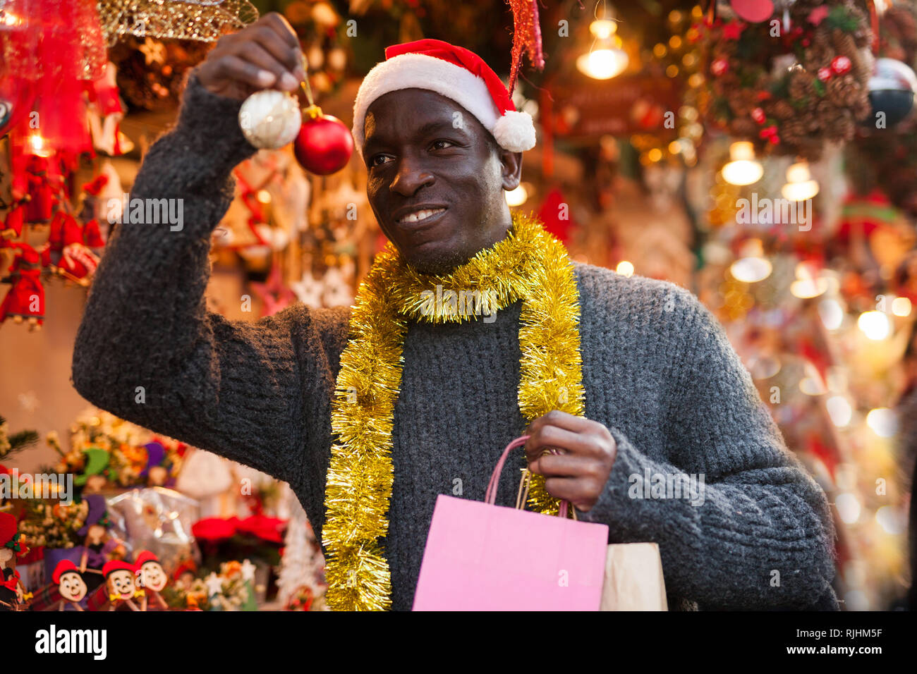 c8efbc6100a53 Smiling African American man in Santa hat selecting festive home decoration  at outdoor Christmas fair -