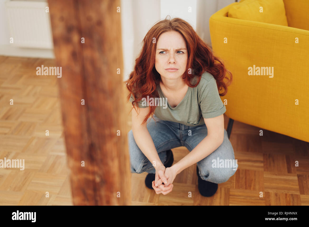 Puzzled young woman crouching down thinking with a serious expression and frown indoors on a parquet floor in her living room - Stock Image