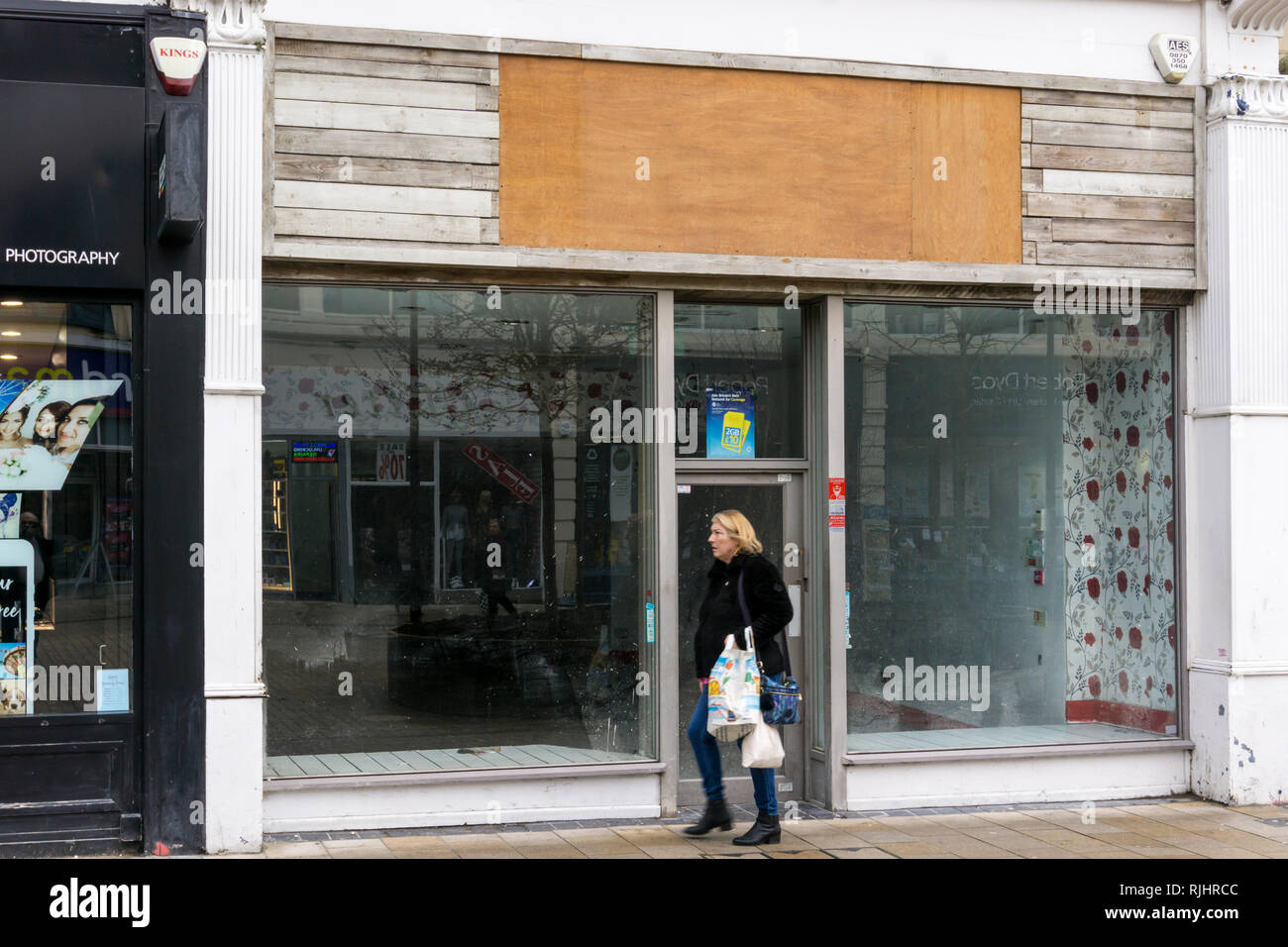 Woman walking past an empty shop in Bromley High Street, South London. - Stock Image