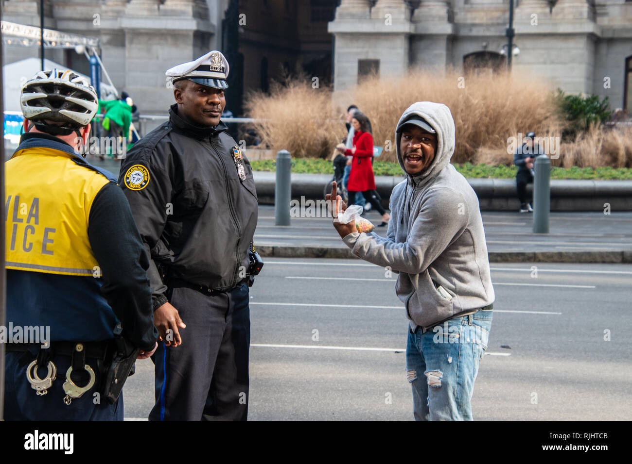 Philadelphia, Pennsylvania - February 5, 2019: Black male in hoodie swears at and gives the middle finger on both hands to a Caucasian police officer  - Stock Image