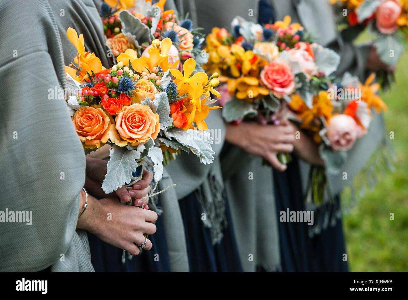 Bridesmaids Holding Their Wedding Bouquets Of Flowers With Yellow