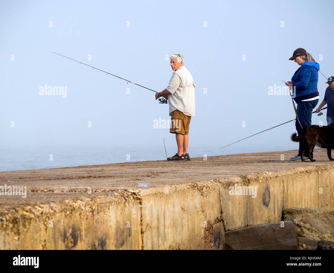A silver-haired man dressed in shirt, shorts and sandals fishes from the south jetty on a foggy, February day in Port Aransas, Texas USA. - Stock Image