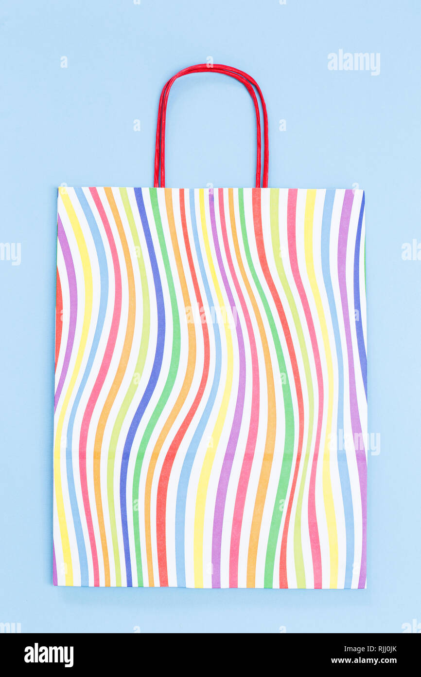 Colorful paper bag on blue background - Stock Image