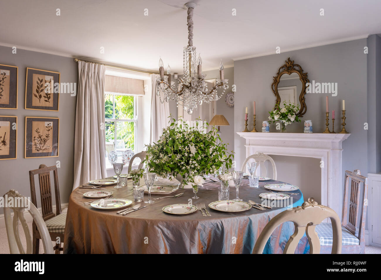Burlington fireplace and restored French chandelier from Hattie Hatfield Decorative Antiques & Interiors. - Stock Image