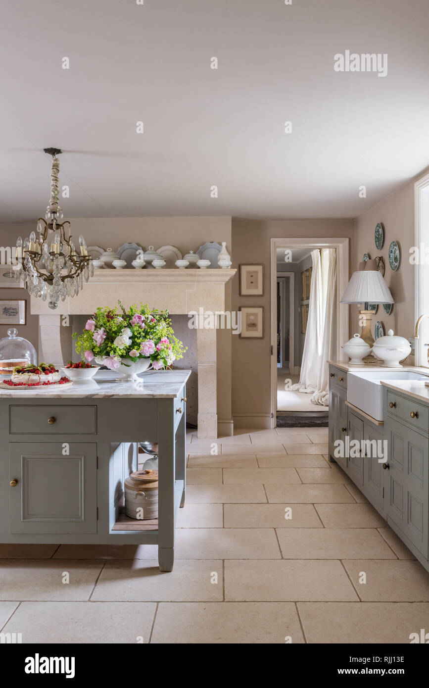 Bespoke cabinets from Mark Goodacre Kitchens painted in  50/50 mix of Farrow & Ball's Hardwick White and Pigeon. The flooring is from Mandarin Stone. - Stock Image