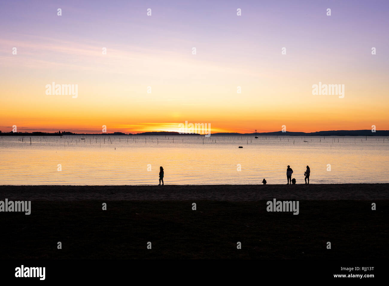 Group of people walking on the beach at sunset. Beautiful marine landscape with calm sea. Rias Baixas, Galicia, Spain - Stock Image