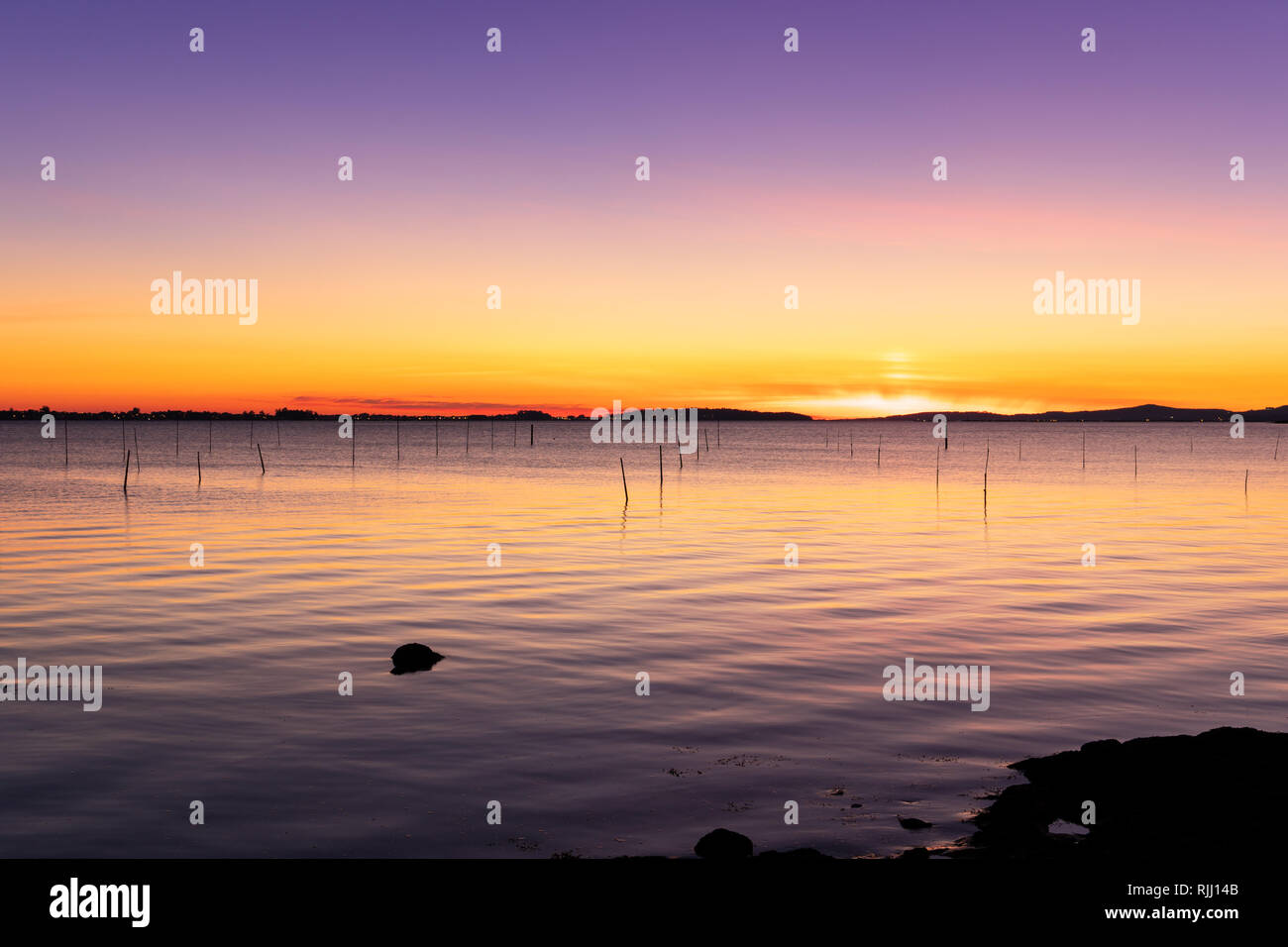 Beach sunset with calm sea scene in Galicia, Spain. Beautiful marine landscape - Stock Image