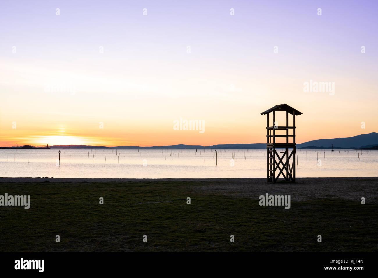 Lifeguard rescue tower on beach at sunset. Beautiful Marine landscape. Rias Baixas, Galicia, Spain - Stock Image