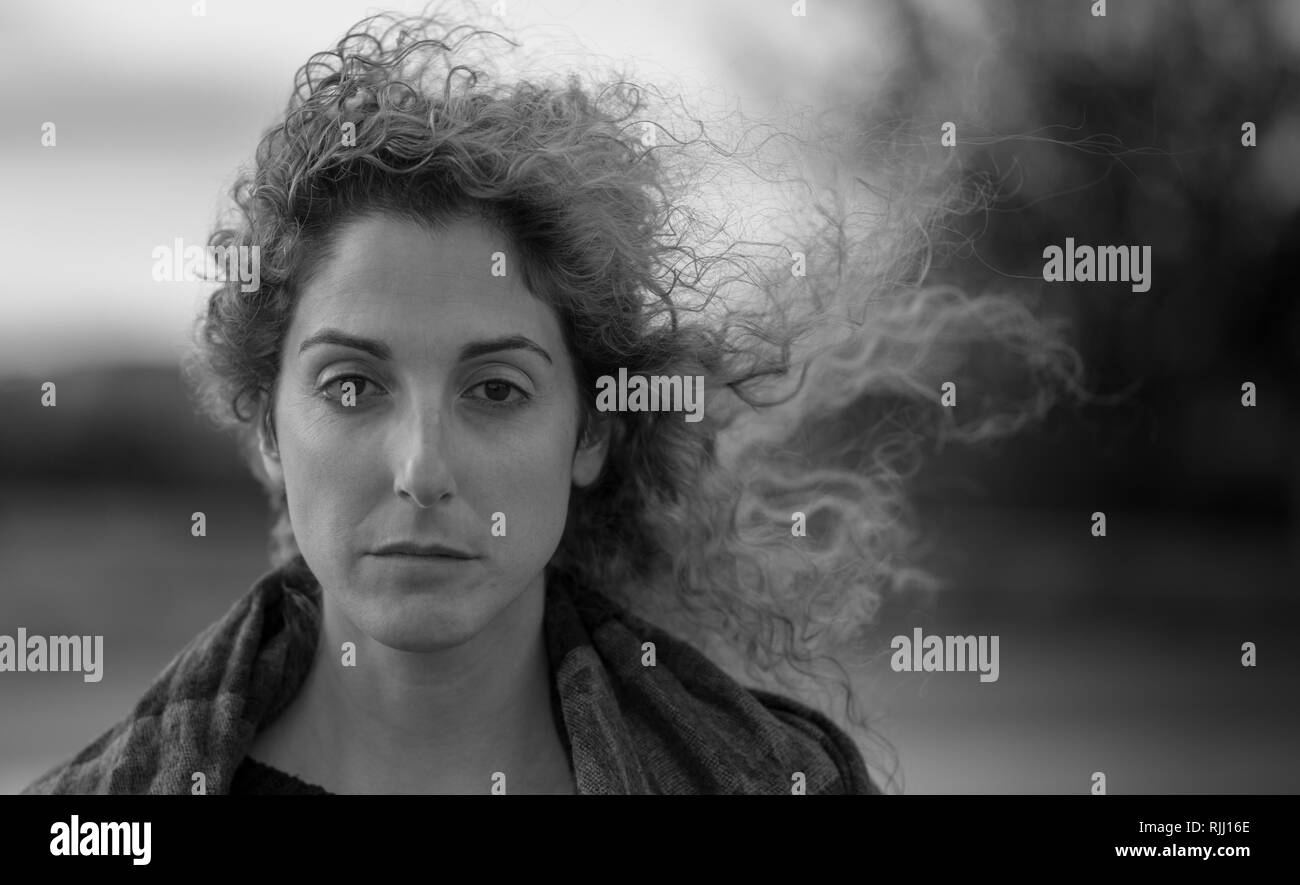Black and white portrait of woman with windswept hair blowing to the side with fixed stare
