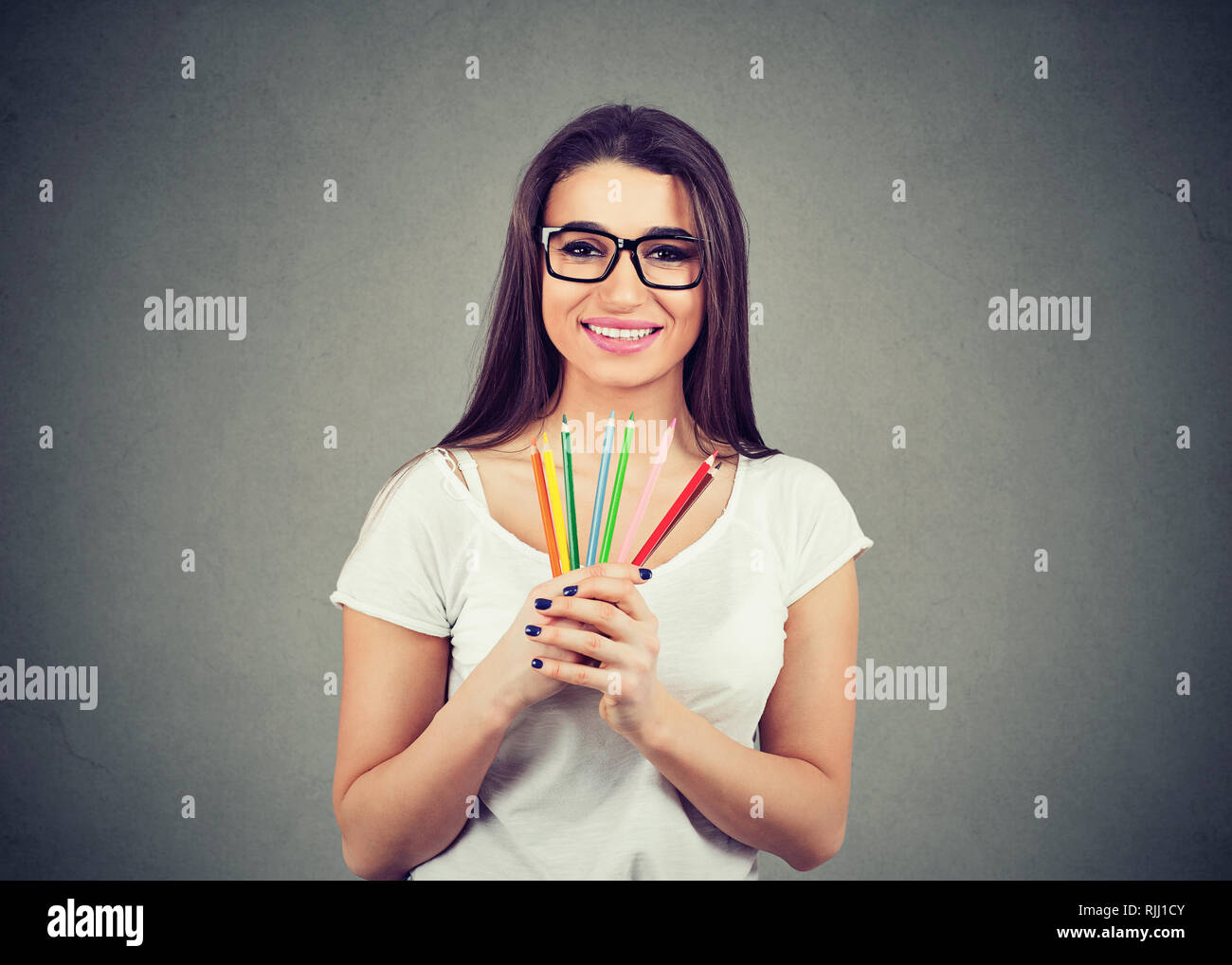 Cheerful excited young woman holding colorful crayon pencils isolated on gray wall background. Stock Photo