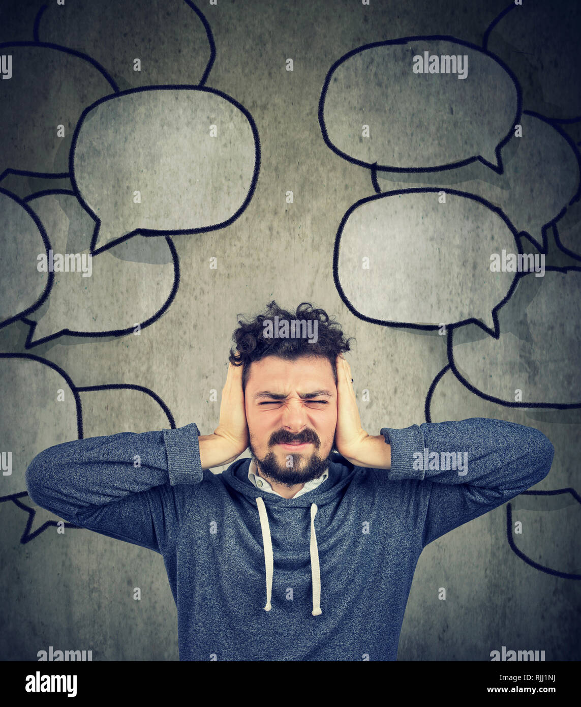Frustrated stressed man covering with hands his ears tired of too much talk around him Stock Photo