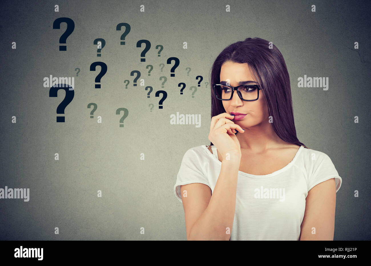 Portrait confused thinking woman bewildered seeks a solution looking preoccupied has many questions isolated on gray wall background - Stock Image