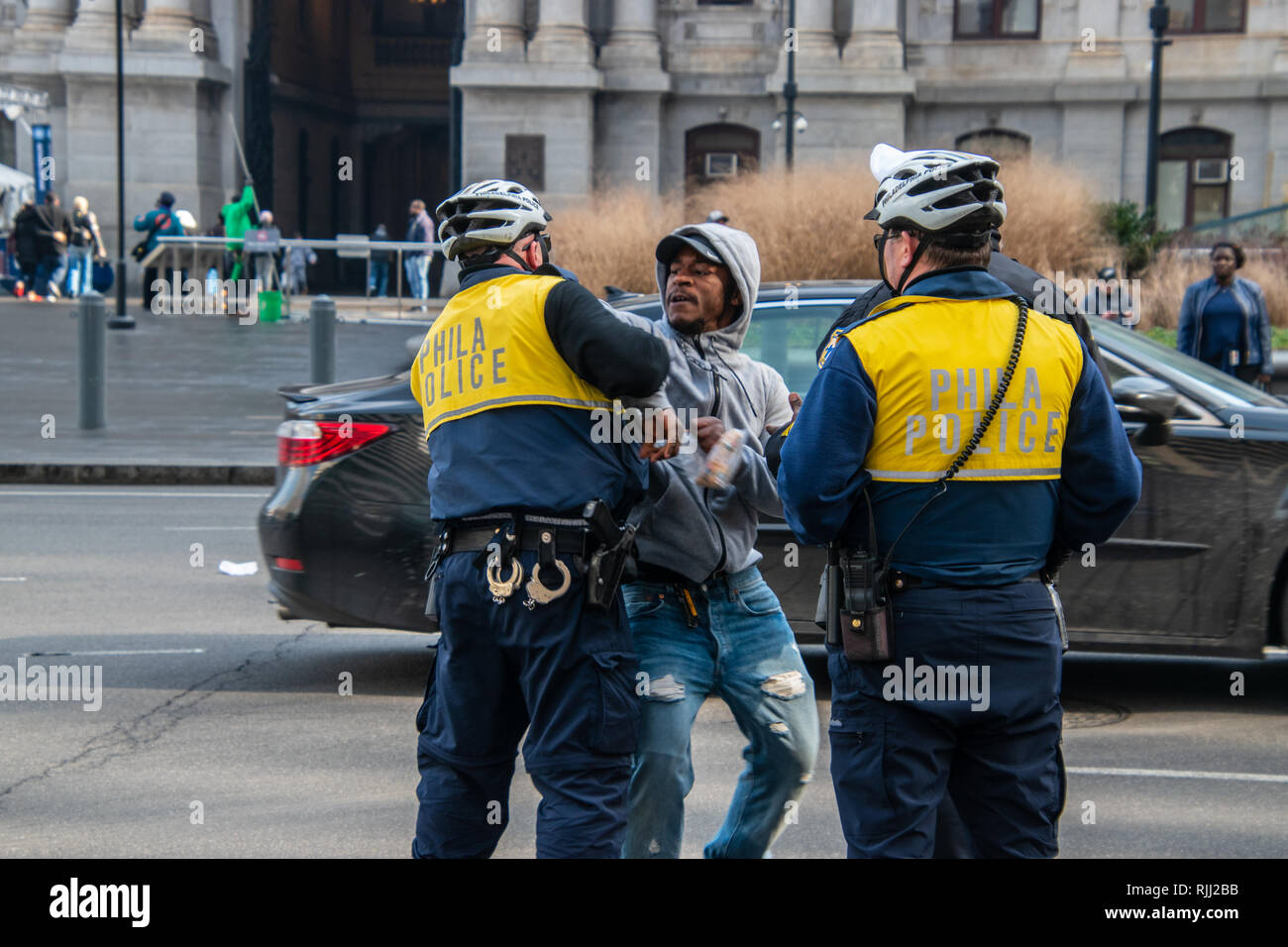 Philadelphia, Pennsylvania - February 5, 2019: Black male is seen here fighting with a Philadelphia police officer during an argument in front of city - Stock Image