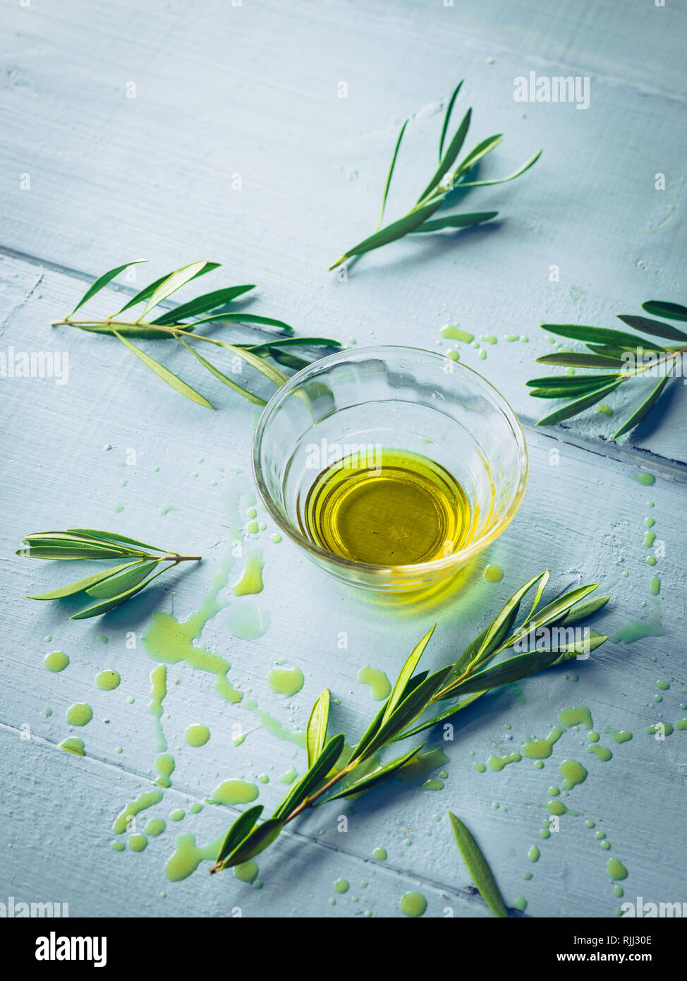 Olive oil with olive twig in a glass bowl - Stock Image