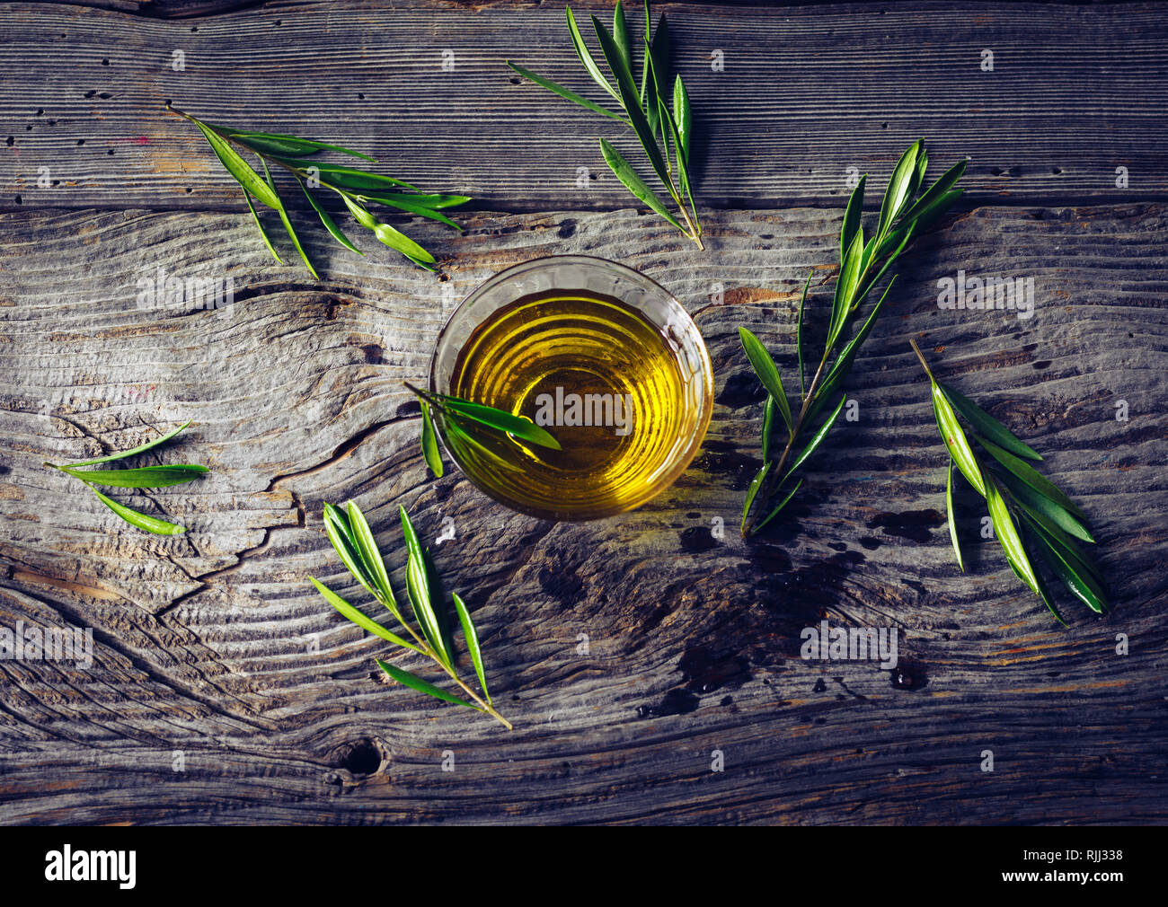 Olive oil with olive twig on rustic wooden table - Stock Image