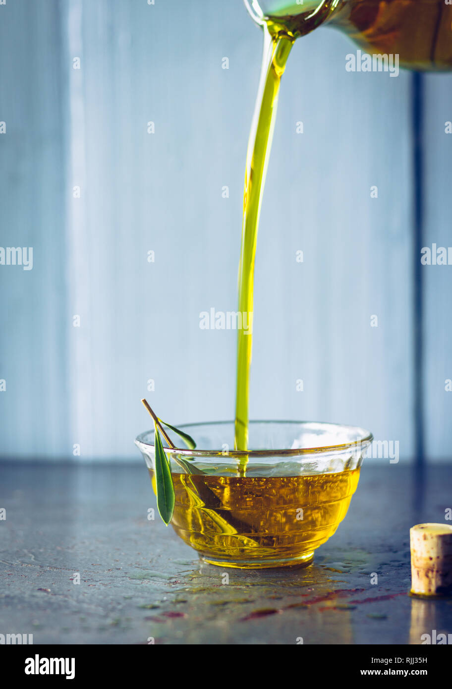 Pouring olive oil into glass bowl with olive twig - Stock Image