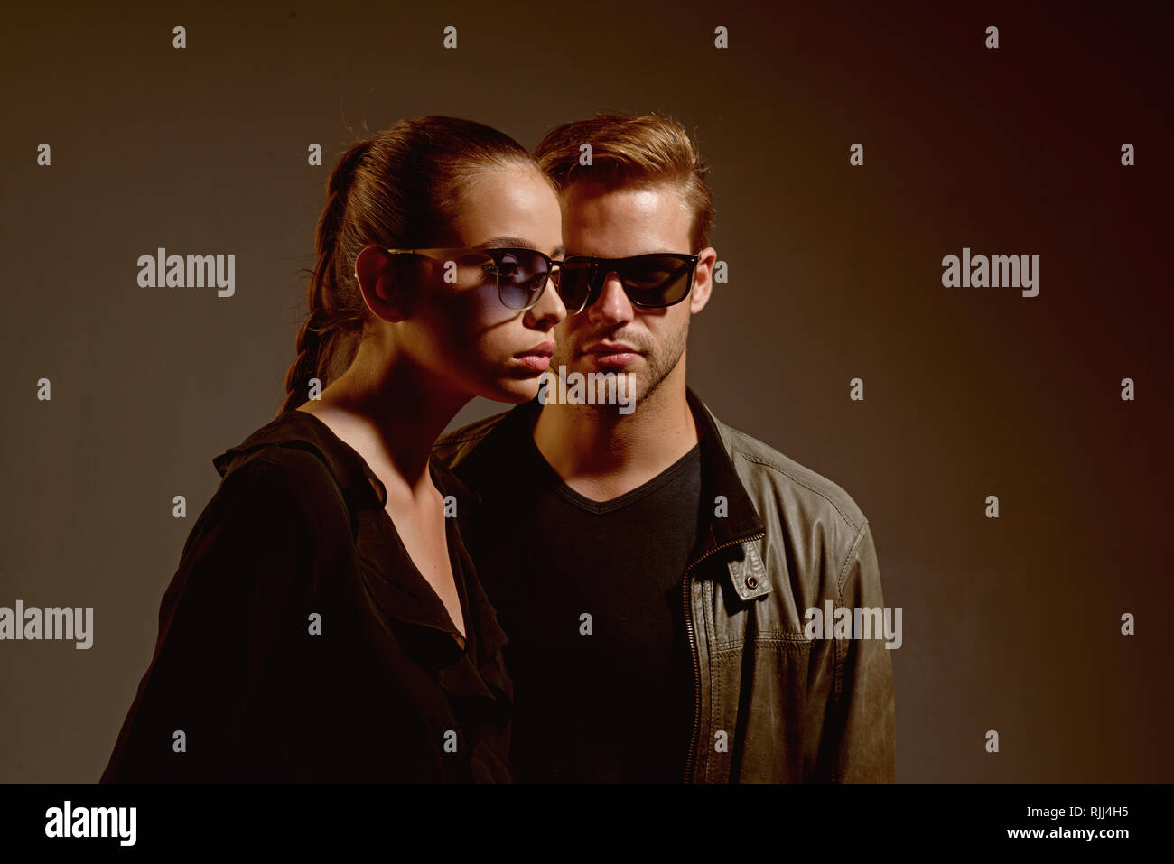 An intellectual look. Fashion models in trendy sun glasses. Couple in love. Couple of man and woman wear fashion glasses. Love relations. Friendship - Stock Image