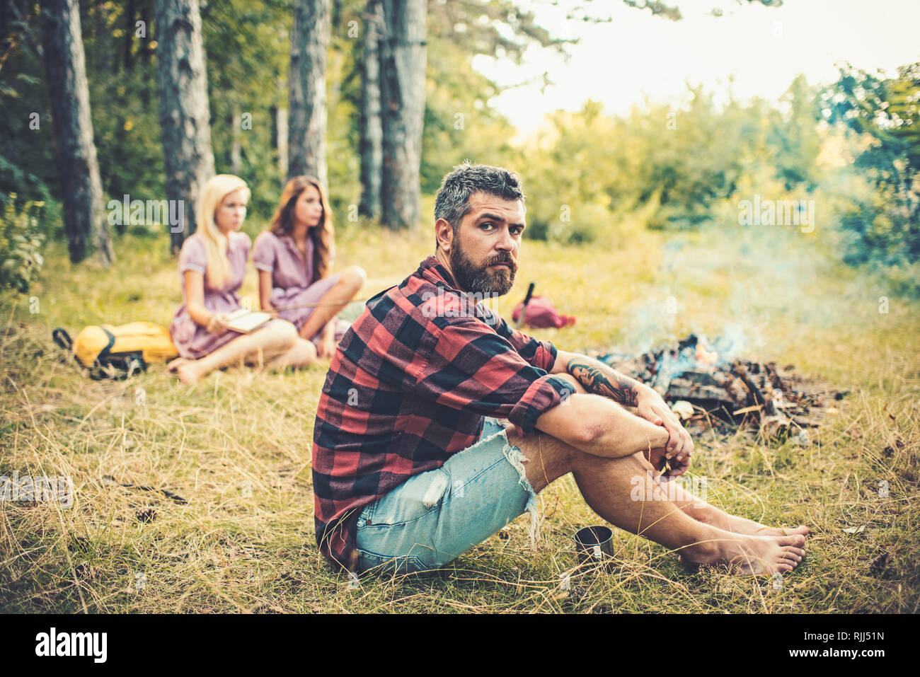 Bearded man relax at bonfire with women on blurred background. Hipster with beard sit at campfire. Friends enjoy camping in forest. Summer vacation - Stock Image