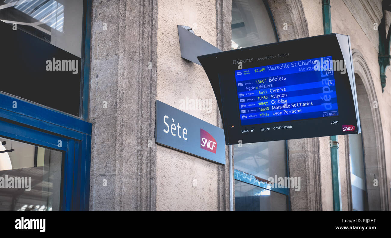 Sete, France - January 4, 2019: LCD display showing the departure of trains in the train station on a winter day - Stock Image