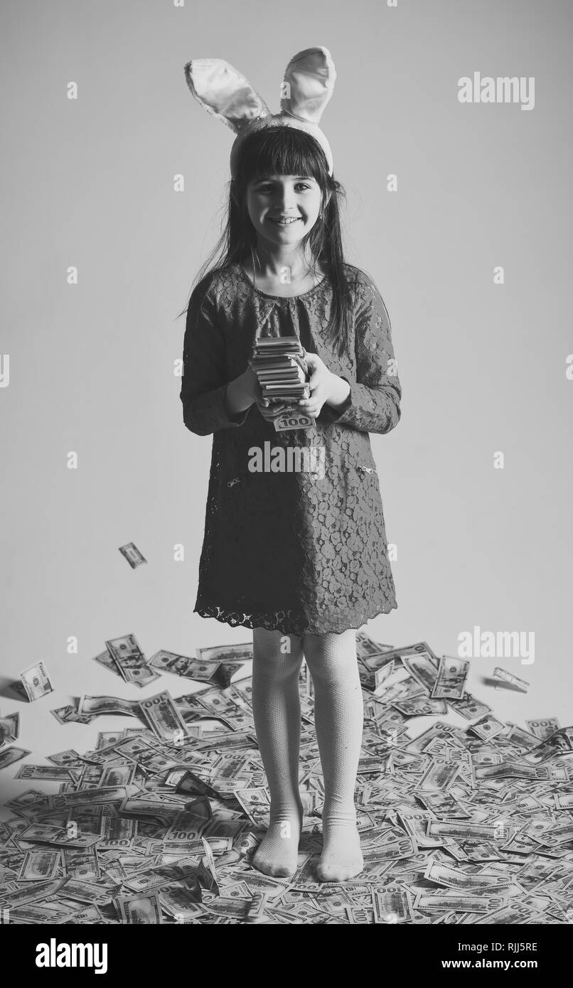 small girl child in bunny ears with many dollars money. - Stock Image