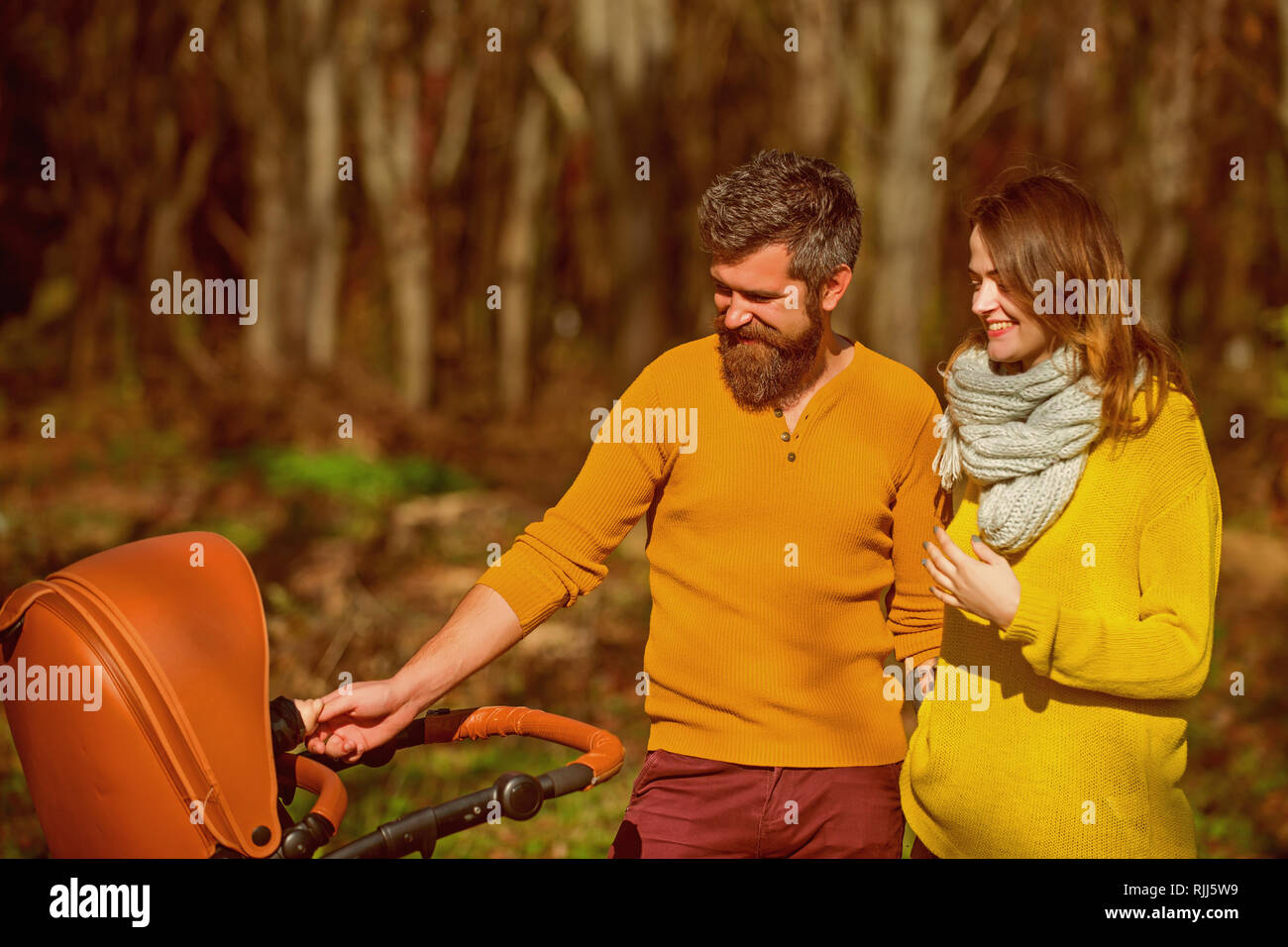 Happy family bond. Woman and man parent push baby stroller while walking through autumn park, family bond. We do it together - Stock Image