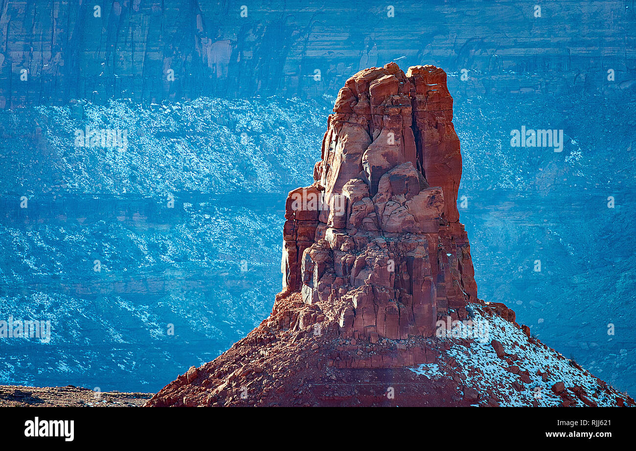 January 2019: A towering spire above the snow covered red sandstone walls and White Rim Trail, Dead Horse Point State Park, Moab, Utah. - Stock Image