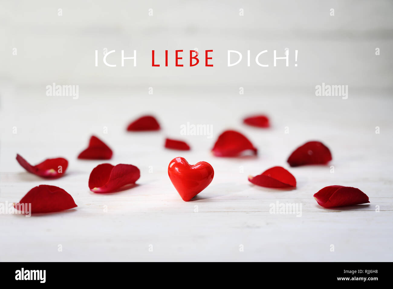 Red Glass Heart Between Rose Petals On A Light Grey Wooden